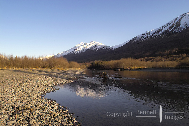 The setting sun casts long shadows across a gravel bar along Eagle River in Anchorage, Alaska.