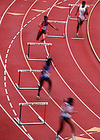 Overview action image of female runners jumping hurdles at a track meet.