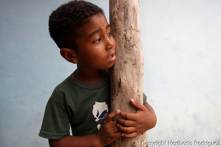 An Afro-Mexican child embraces a tree in his home in Santa Maria Cortijo in the coast of Guerrero state, July 6, 2005.  Afro- Mexicans are considered one of the three ethnic roots that comprise Mexico. Photo by Heriberto Rodriguez