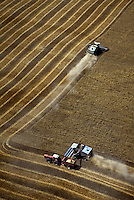 Aerial of 2 combines harvesting wheat field, one is transferring wheat to a wagon pulled by a tractor. Kansas USA Marion County.