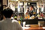 A waiter serves beer at craft beer bar Ushitora in Shimokitazawa, Setagaya Ward, Tokyo, Japan..Photographer: Robert Gilhooly