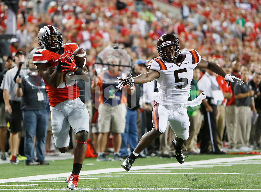 Ohio State Buckeyes cornerback Doran Grant (12) tries for a interception against Virginia Tech Hokies wide receiver Joshua Stanford (5) in the second quarter at OhioStadium September 6, 2014. (Dispatch photo by Eric Albrecht)