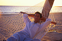 A man relaxes in a hammock at an Oahu beach.