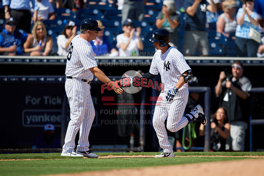 New York Yankees third base coach Phil Nevin (88) congratulates catcher Kyle Higashioka (66) as he rounds the bases after hitting a home run during a Grapefruit League Spring Training game against the Toronto Blue Jays on February 25, 2019 at George M. Steinbrenner Field in Tampa, Florida.  Yankees defeated the Blue Jays 3-0.  (Mike Janes/Four Seam Images)