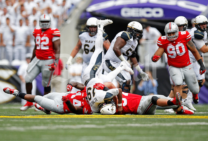 Ohio State Buckeyes defensive lineman Joey Bosa (97), right, and Ohio State Buckeyes linebacker Curtis Grant (14), left, sack Navy Midshipmen quarterback Keenan Reynolds (19) during the third quarter of the college football game between the Ohio State Buckeyes and the Navy Midshipmen at M&T Bank Stadium in Baltimore, Saturday afternoon, August 30, 2014. The Ohio State Buckeyes defeated the Navy Midshipmen 34 - 17. (The Columbus Dispatch / Eamon Queeney)
