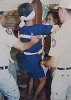 A 65 year-old heroin smuggler is man-handled onto the the wooden execution cross in Thailand's exection chamber minutes before being shot to death. Thailand's only executioner Chawalate Jarubun of Bangkwang Central Prison has executed 55 prisoners.