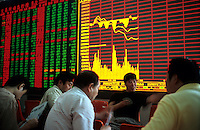 Stock traders play card in front of the board at a stock exchange July, 15, 2005 in Beijing, China.  (Lou Linwei/Sinopix)