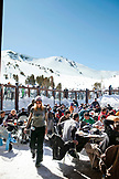 USA, California, Mammoth, skiers and snowboarders take a break and sit outside the lodge at Mammoth Ski Resort