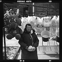 A game stall worker waits for customers at a temple fair during the Chinese New Year in Beijing, China, February, 2013. (Mamiya 6, 75mm, Kodak TRI-X film)