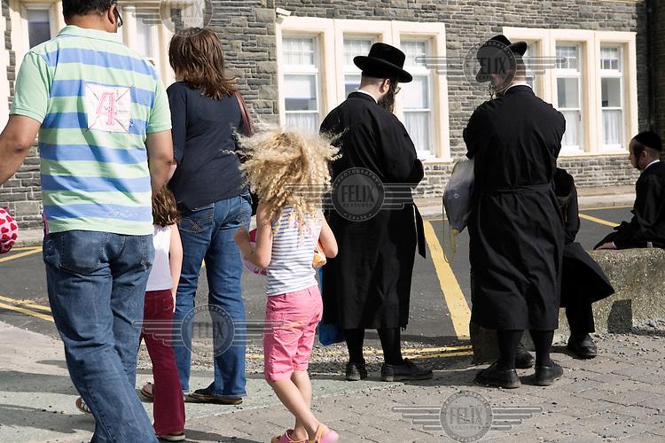 Aberystwyth locals pass an Hasidic family on the promenade.