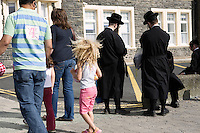 Aberystwyth locals pass an Hasidic family on the promenade.