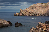 """Spain. Balearic Islands. Minorca (Menorca). Fornells. Cap de Sa Paret. The small rocky island is called """"Escull de Tirant"""". A motor boat from Menorca Nord company is taking tourists for a sightseeing tour around coves. Rocks and cliffs in the Mediterranean Sea. Fornells is a village located in a bay in the north of the Balearic island of Menorca. Fornells is part of the autonomous community of the Balearic. In Spain, an autonomous community is a first-level political and administrative division, created in accordance with the Spanish constitution of 1978, with the aim of guaranteeing limited autonomy of the nationalities and regions that make up Spain. 9.09.2019 © 2019 Didier Ruef"""