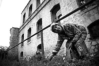 "Nagorny-Karabach, 14.05.2011, Shushi. Eine Frau sammelt Kr?uter in einem Garten vor den Ruinen der Stadt...""The Twentieth Spring"" - ein Portrait der s¸dkaukasischen Stadt Schuschi, 20 Jahre nach der Eroberung der Stadt durch armenische K?mpfer 1992 im B¸gerkrieg um die Unabh?ngigkeit Nagorny-Karabachs (1991-1994). A woman picks some herbs in front of ruins. ""The Twentieth Spring"" - A portrait of Shushi, a south caucasian town 20 years after its ""Liberation"" by armenian fighters during the civil war for independence of Nagorny-Karabakh (1991-1994)..Une femme ramasse quelques herbes en face des ruines. ""Le Vingtieme Anniversaire"" - Un portrait de Chouchi, une ville du Caucase du Sud 20 ans après sa «libération» par les combattants arméniens pendant la guerre civile pour l'indépendance du Haut-Karabakh (1991-1994).. © Timo Vogt/Est&Ost, NO MODEL RELEASE !!"