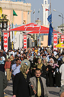 Tripoli, Libya, North Africa - Libyan Men, Women, Families at International Trade Fair.  Clothing Styles.  Minaret in Background.