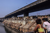 Sao Paulo, Brazil. Favela shanty town by the Tiete river showing pollution and rubbish; two girls.