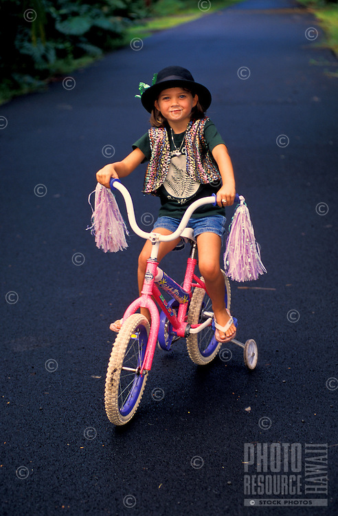 Little girl dressed up with hat riding a bike