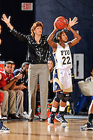 21 January 2012:  FIU guard Jerica Coley (22) handles the ball while FAU Head Coach Chancellor Dugan signals to her players in the first half as the Florida Atlantic University Owls defeated the FIU Golden Panthers, 50-49, at the U.S. Century Bank Arena in Miami, Florida.
