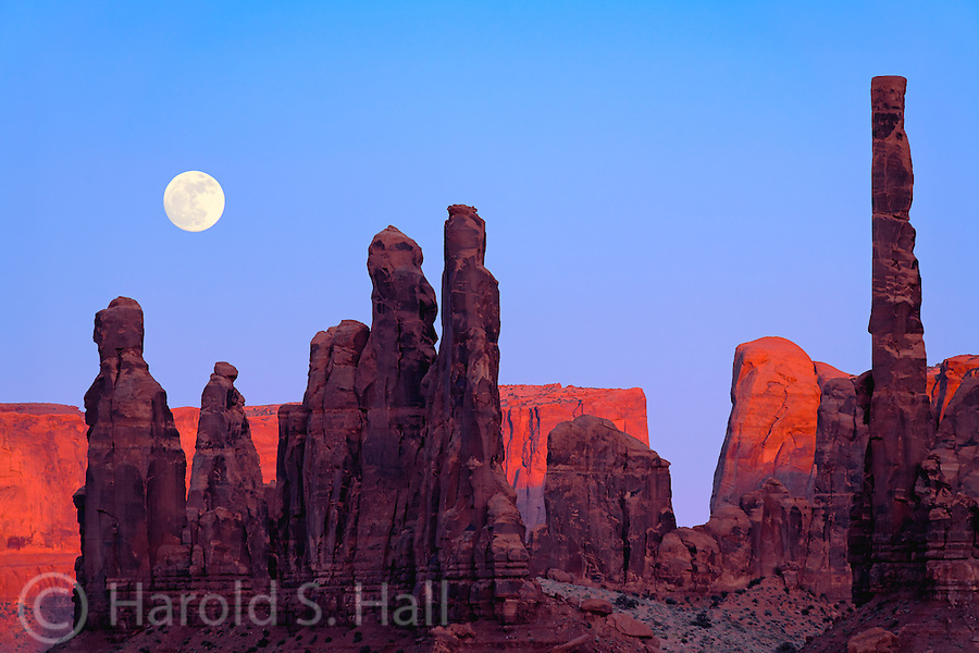 A full moon rises behind the totem poles in Monument Valley, Utah.  Monument Valley lies on the boarder of Utah and Arizona, near the four corners region. It was made famous by film director John Ford in his western movies. These sandstone buttes are over 1,000 feet tall.