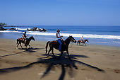 Osa Peninsula, Costa Rica. Group of tourists riding horses on the beach at Drake Bay.