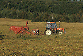 Farm tractor  with a pull-type combine thrashing an oat field