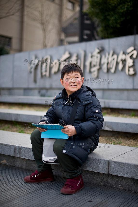 Un bimbo in una strada di Hangzhou.<br /> A boy seat in the center of Hangzhou