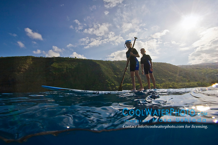 Young boys standing up on SUB (stand up paddleboard), Kealakekua Bay, Big Island, Hawaii, Pacific Ocean.
