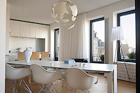A white lacquered aluminium table is placed on the diagonal in this kitchen/dining area with impressive views over the roofs of Paris