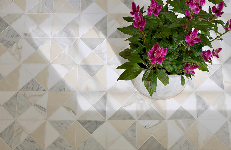 Christopher, a hand-cut mosaic shown in honed Bianco Antico, Carrara, and Calacatta Tia, is part of the Illusions® collection by New Ravenna.