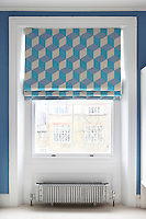 A blind patterned with a blue and white cube design in a child's bedroom