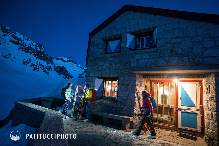 Ski tourers with headlamps on getting ready to leave the Bächlital Hut for the Gauli Hut while on the Berner Haute Route, Switzerland