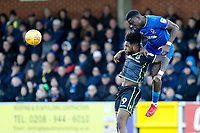 Adedeji Oshilaja of AFC Wimbledon beats Ellis Harrison of Bristol Rovers to the ball during the Sky Bet League 1 match between AFC Wimbledon and Bristol Rovers at the Cherry Red Records Stadium, Kingston, England on 17 February 2018. Photo by Carlton Myrie.