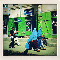 Two boys walk along a road behind two burqa clad women passing a tailor's shop.