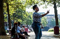 Nederland, Amsterdam,  14-08-2016  <br /> Meisje gebaart dwingend terwijl zij in haar telefoon schreeuwt. <br /> <br /> Photo: Til &amp; Wijnbergh