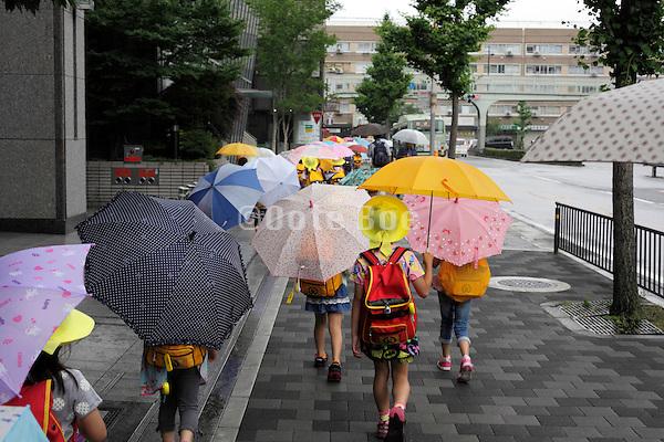 little school children walking with bright colored umbrellas Japan