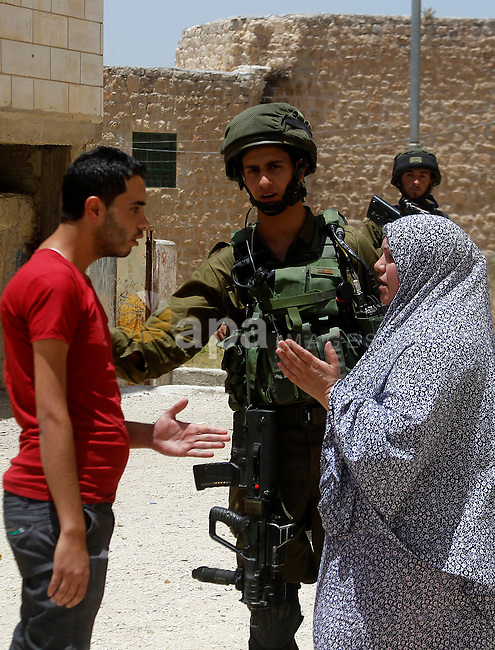 A Palestinian woman argues with Israeli troops during a Palestinian man was detain by Israeli troops who the Israeli military said that he was throw a molotov cocktail, in the West Bank city of Hebron 01 June 2016. Photo by Wisam Hashlamoun