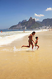 BRAZIL, Rio de Janiero,  two kids run out of the water at Ipanema Beach, which is located bewteen Leblon and Arpoador