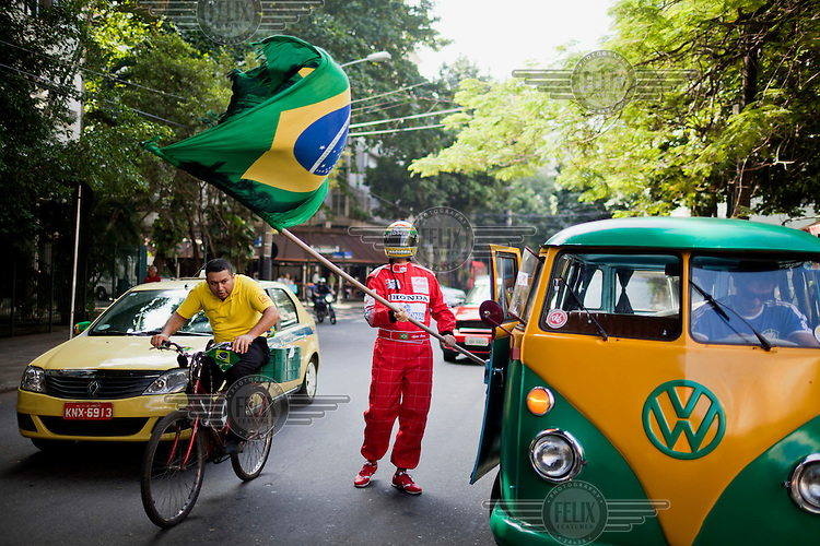 A 1973 Volkeswagon Kombi decorated in Brazil's colours, green and yellow, on the day Brazil played Mexico during the FIFA 2014 World Cup. Waving a Brazilian flag beside the vehicle is Fabio Gabry, dressed as the famous Brazilian Formula One champion, Ayrton Senna.
