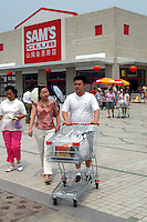 Customers walk out of Sam's Club in Beijing after shopping. Wal-Mart, the biggest retailling outlet in US, opens it's first hyermarket in Beijing, China.