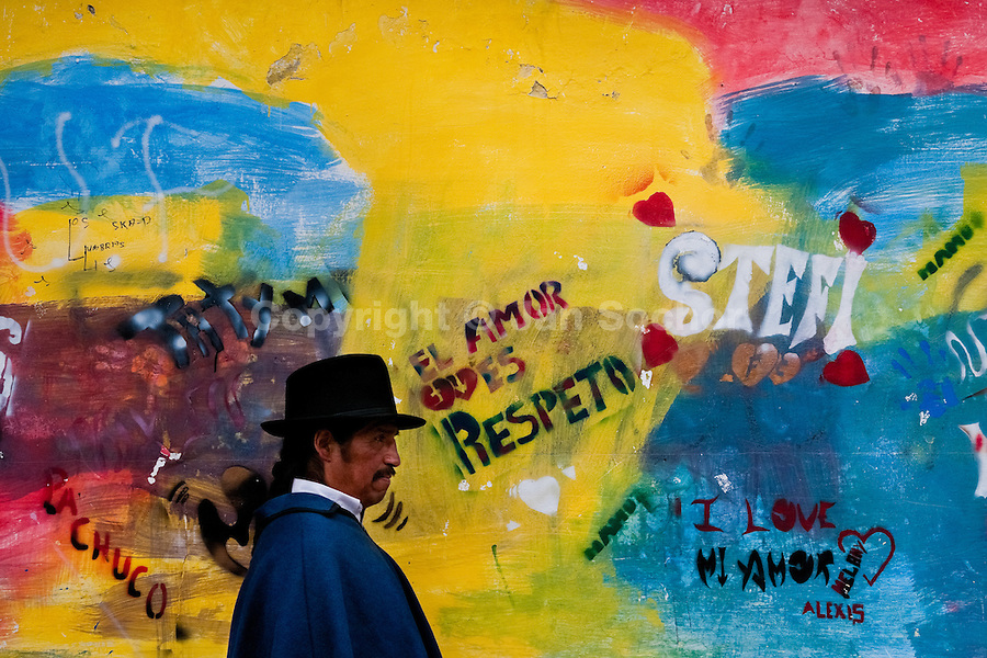 "A man passes in front of a colorfully paited wall during the Inti Raymi fiesta in Pichincha province, Ecuador, 26 June 2010. Inti Raymi, ""Festival of the Sun"" in Quechua language, is an ancient spiritual ceremony held in the Indian regions of the Andes, mainly in Ecuador and Peru. The lively celebration, set by the winter solstice, goes on for various days. The highland Indians, wearing beautiful costumes, dance, drink and sing with no rest. Colorful processions in honor of the God Inti (Sun) pass through the mountain villages giving thanks for the harvest and expressing their deep relation to the Mother Earth (Pachamama)."