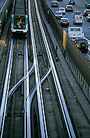 Man driving a subway train while looking across at traffic on the road parallel, Paris, France.