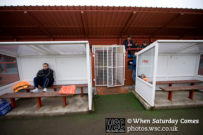 Workington AFC 0 Boston United 1, 24/02/2008. Borough Park, Blue Square North. One of the home team's substitutes waiting for the teams to come out prior to the Blue Square North fixture between hosts Workington AFC (red) and Boston United at Borough Park. The visitors won with a solitary sixth-minute goal by Jon Rowan in front of 388 spectators. Both Workington AFC and Boston United were members of the Football League, the Cumbrians losing League status in 1977 while the Lincolnshire club were relegated in 2007 and demoted two divisions for financial irregularities. Photo by Colin McPherson.