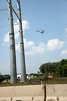 Helicopter stringing high tension electric wires between tall towers next to Freeway 94. Alexandria Minnesota MN USA