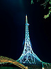 The Arts Centre spire, lit up at night.