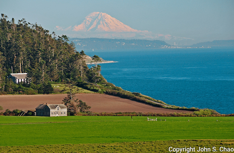 View of Ferry House at Ebey's Landing National Historical Reserve, Whidbey Island, Washington State. Puget Sound, Mt. Rainier and Seattle skyline in backdrop.