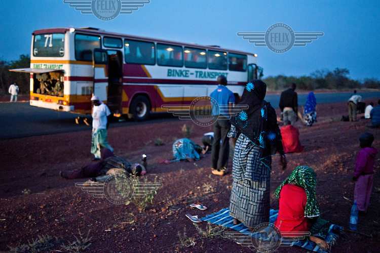 At sunset a bus travelling from Bamako to Mopti stops at the roadside to allow passengers pray.