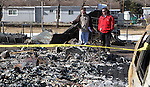Insurance investigator John Yeager, left, surveys the home of Patrick and Jeannie Watts on Saturday, Jan. 21, 2012, in Pleasant Valley, south of Reno, Nev., after it was destroyed in Thursday's brush fire. Jeannie's mother June Hargis, 93, and their three horses died in the fire. .Photo by Cathleen Allison