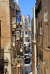 Narrow street historic housing with traditional balconies in city centre of Valletta, Malta