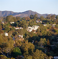 View from the house over the wooded residential hillside with the mountains in the distance