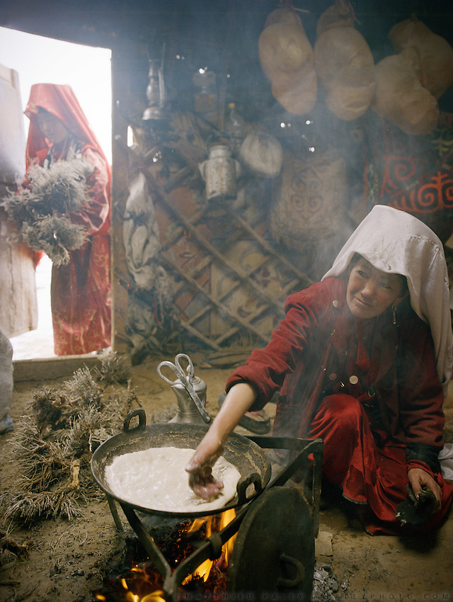 "Ustad Ghulam's wife cooking nan bread in the kitchen yurt..Campment of ""second"" Sary Tash..Winter expedition through the Wakhan Corridor and into the Afghan Pamir mountains, to document the life of the Afghan Kyrgyz tribe. January/February 2008. Afghanistan"