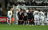Pictured: A scuffle breaks out between Swansea and Barnsley players after the foul of Garry Monk (3rd L)  of Swansea against Mounir El Haimour of Barnsley while waiting for Barnsley to take a penalty, referee G D Horwood (2nd L) is showing a yellow card to Monk.<br /> Re: Coca Cola Championship, Swansea City FC v Barnsley at the Liberty Stadium. Swansea, south Wales, Tuesday 09 December 2008.<br /> Picture by D Legakis Photography / Athena Picture Agency, Swansea 07815441513